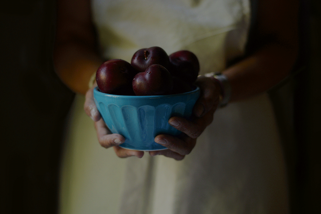 Woman holding a bowl of fruit. Are you busy or productive?
